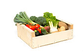 Wooden crate filled with a variety of fresh, ripe, farm-grown vegetables including leeks, broccoli, lettuce, tomatoes, sweet potatoes, zucchini, fennel, potatoes, and onions cut-out
