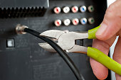 Hand useing wirecutters and cutting a television cable attached to a television set. Wirecutters cut the cable wire.