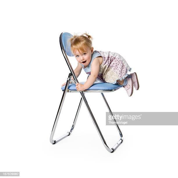 かわいい 15 ヶ月ガールクライミングして、ブルーの椅子