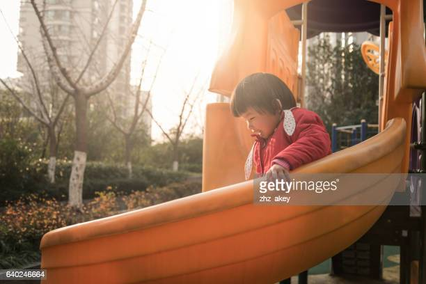 Cute 3 year old Asian girl playing on playground slide