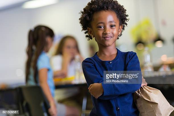 Cute African American girl holding paper lunch sack in cafeteria