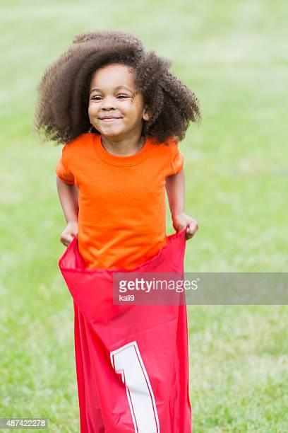 Cute African American girl in potato sack race