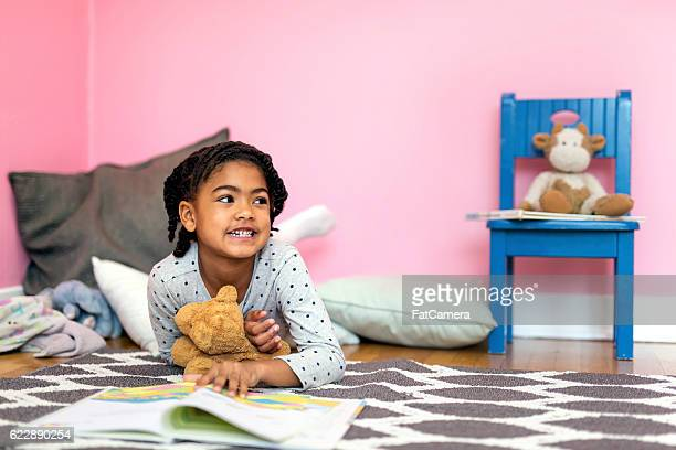 Cute African American girl reading a book with her