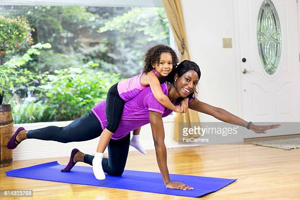 Cute African American girl sitting on moms back as