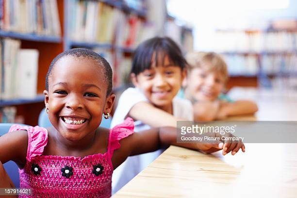 Cute African American girl with friends in the library