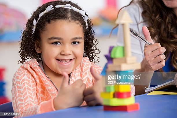 Cute African American preschool girl giving the thumbs up