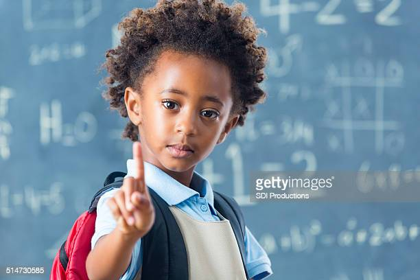 Cute African American private school child holding up one finger