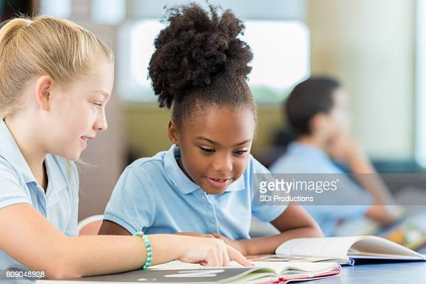 Cute African American schoolgirl reading a book with Caucasian friend