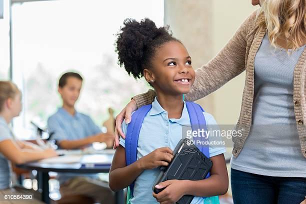 Cute African American schoolgirl talks with teacher before class