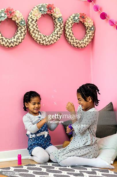 Cute African American sisters blowing bubbles and laughing together