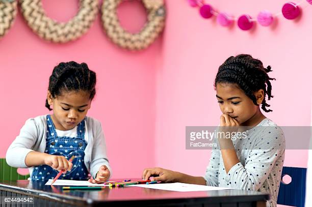 Cute African American sisters drawing at a table