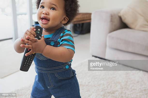 Cute Afro baby holding remote control in living room