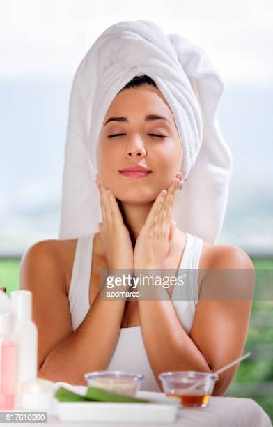 Cute and happy Hispanic young woman applying aloe vera moisturizer on her face.