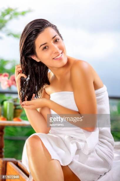 Mignonne et joyeux hispanique jeune femme faisant des traitement de cheveux soi après bain