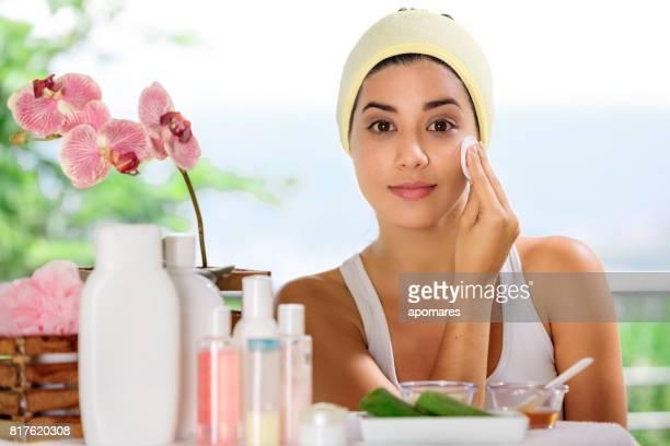 Mignonne et joyeux hispanique jeune femme regardant la caméra tout en nettoyant son visage avec une serviette en coton.