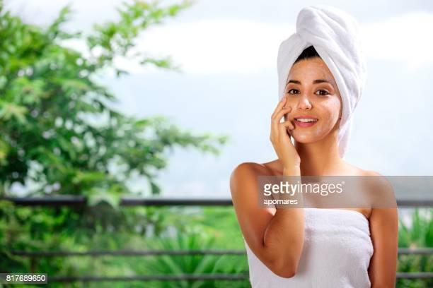 Mignonne et joyeux hispanique jeune femme regardant la caméra avec facial afterbath Klos et towelhead