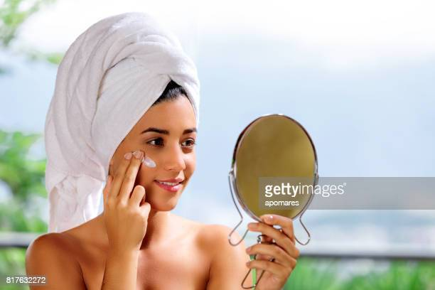 Cute and happy Hispanic young woman looking at camera with towelhead afterbath