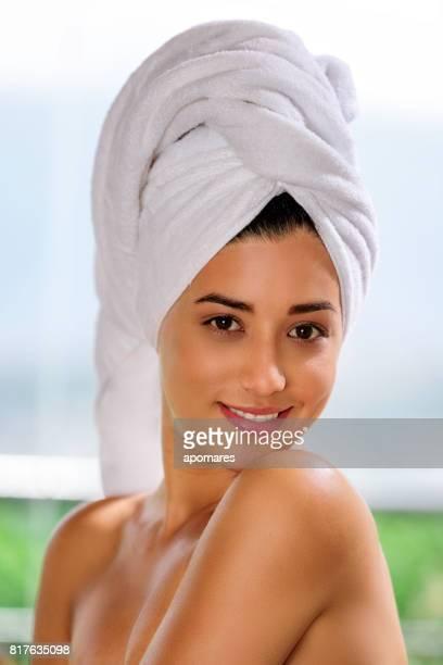 Mignonne et joyeux hispanique jeune femme regardant la caméra avec towelhead afterbath