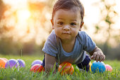 Cute asian baby crawling in the green grass and colorful ball - Sunset filter effect