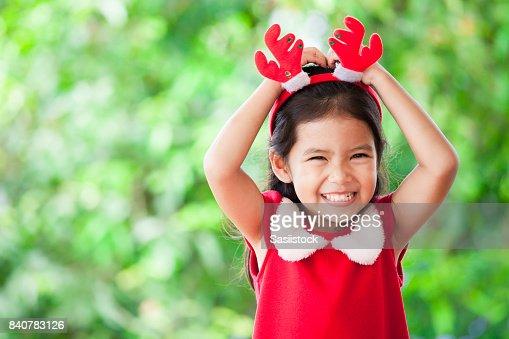 Vestido de la muchacha de lindo niño Asiático en Navidad sonriendo sobre fondo verde de la naturaleza : Foto de stock