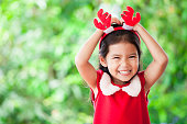 Cute asian child girl in christmas dress smiling on green nature background. Love and Christmas concept