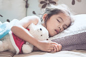 Cute asian child girl sleeping and hugging her teddy bear in the bed