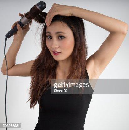 Cute Asian girl curling hair : Stock Photo