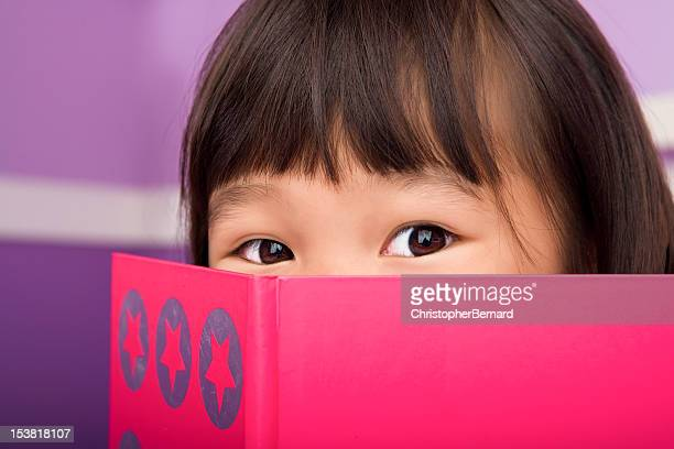 Cute asian girl reading in bedroom