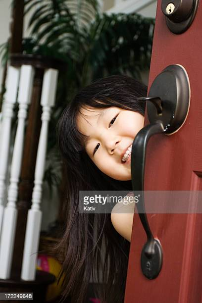 Cute Asian Girl Welcoming Behind Door