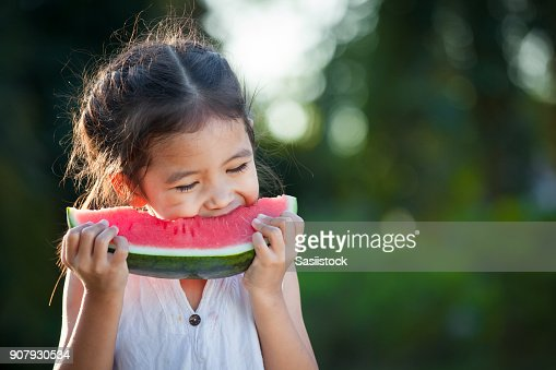 Cute asian little child girl eating watermelon fresh fruit in the garden : Foto de stock