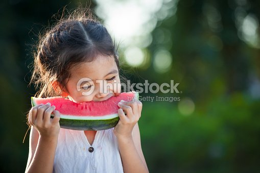 Cute asian little child girl eating watermelon fresh fruit in the garden : Stock Photo