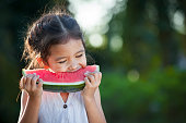 Cute asian little child girl eating watermelon fresh fruit in the garden