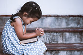 Cute asian little girl closed her eyes and  folded her hand in prayer on a Holy Bible for faith concept in vintage color tone