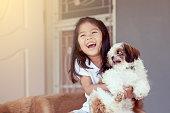 Cute asian little girl with her Shih Tzu dog in vintage color tone