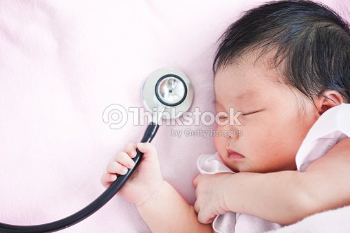 7848f254c Cute asian newborn baby girl sleeping and holding medical stethoscope in  hand : Stock Photo
