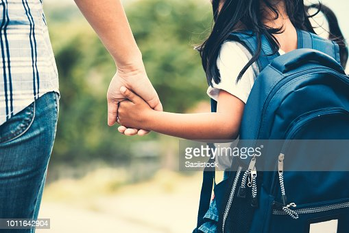 Cute asian pupil girl with backpack holding her mother hand and going to school : Foto de stock