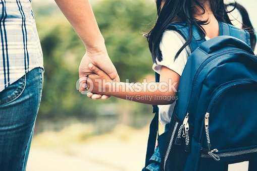 Cute asian pupil girl with backpack holding her mother hand and going to school : Stock Photo