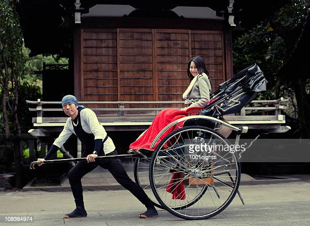 Cute asian woman pulled by a rickshaw