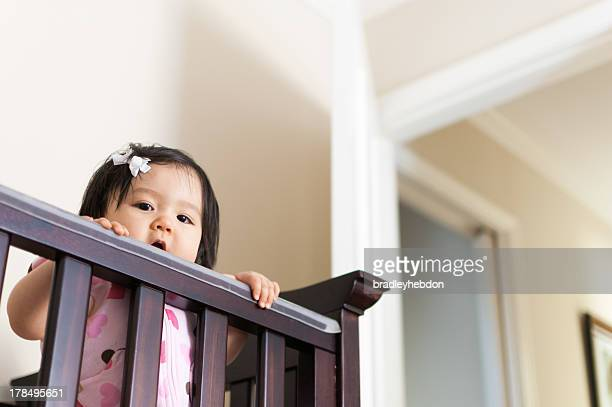 Cute Baby Asian girl peering out from her crib