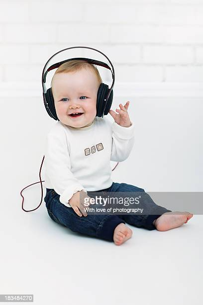 Cute baby boy in headphones listening to music