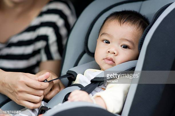 Cute baby boy in safety seat.
