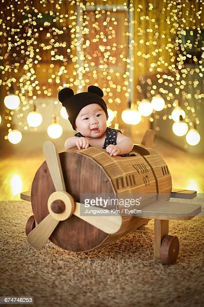 Cute Baby Boy In Wooden Toy Airplane By Illuminated Light Bulbs At Home