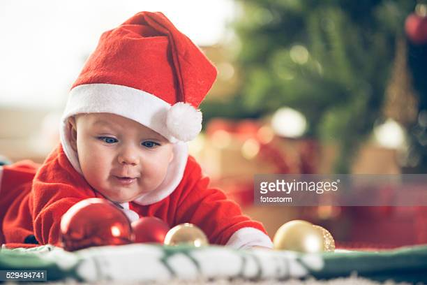 Cute baby boy playing with Christmas baubles