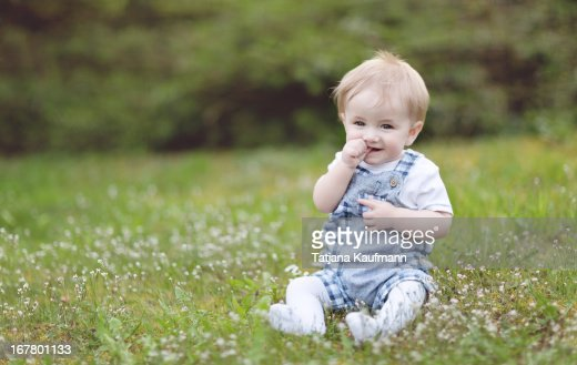 Cute Baby Boy sitting in Grass in Spring, smiling : Stock Photo