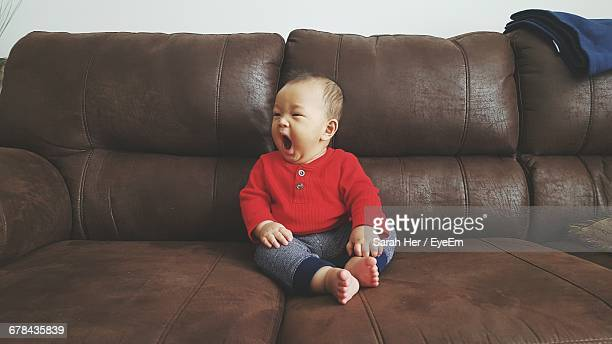 Cute Baby Boy Yawning While Sitting On Sofa At Home