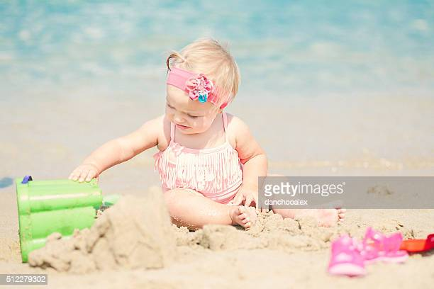 Cute baby girl at the beach playing with sand