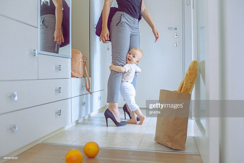 Cute baby girl cuddle with her mom hugging her legs