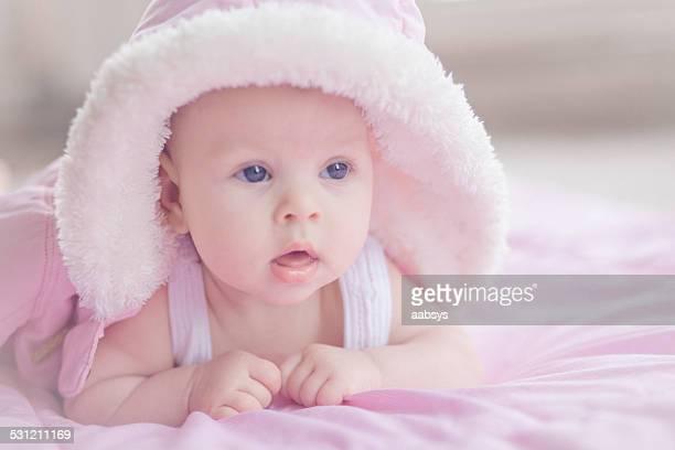 Linda niña bebé caer en su estómago cubierto con chaqueta de vestir