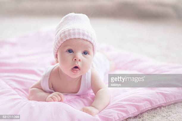 Cute baby girl lying at her stomach looking above