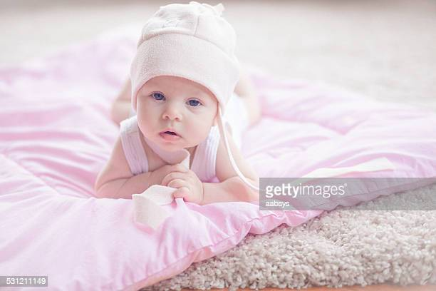 Cute baby girl lying at her stomach looking at camera